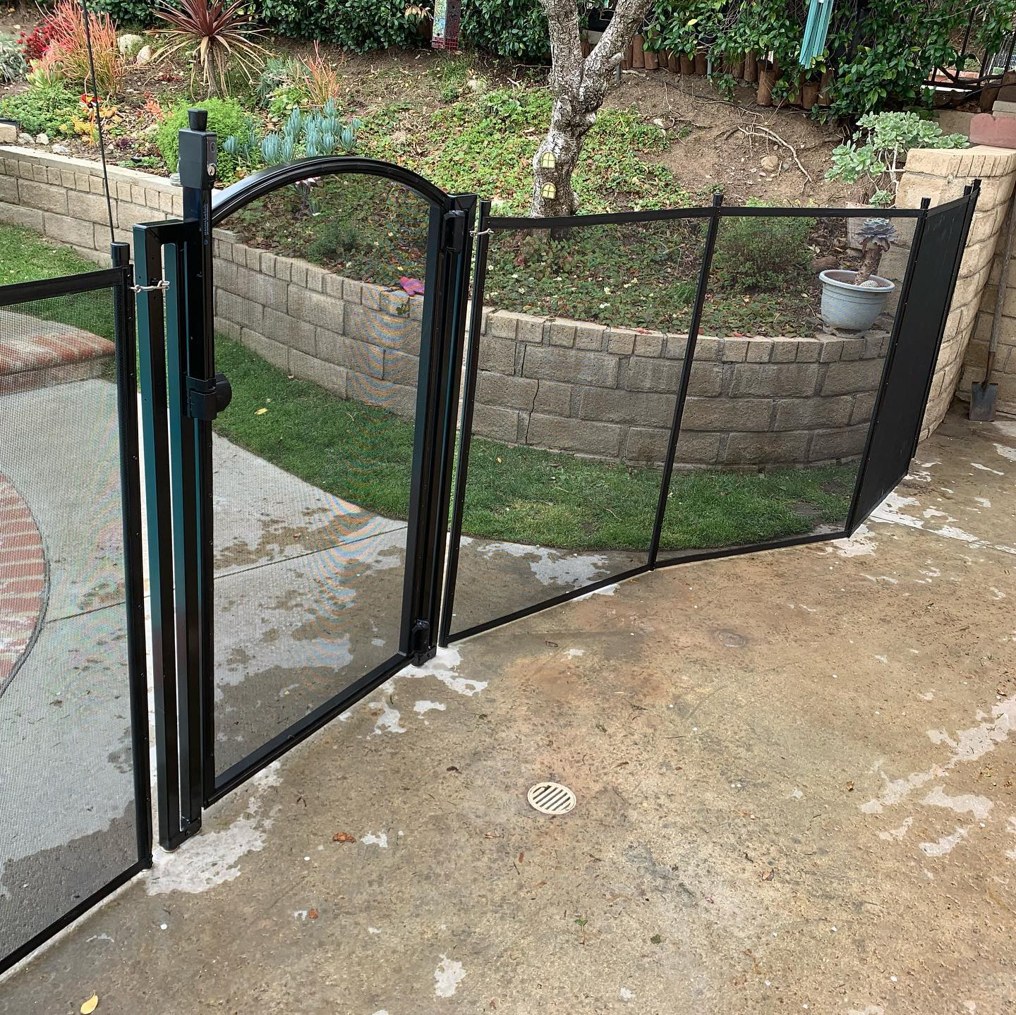black mesh pool fence with self-closing arched style pool gate